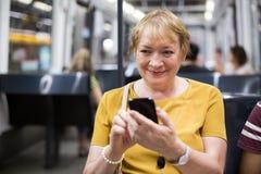 Senior woman in subway phone Stock Photos