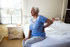 Senior woman suffering from backache in the bedroom Royalty Free Stock Image