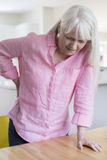 Senior Woman Suffering From Backache Whilst Getting Out Of Chair Stock Photo