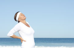 Senior woman suffering backpain sky background. Active and attractive looking senior woman  suffering backpain,  with blue sky and ocean as background and copy Royalty Free Stock Photo
