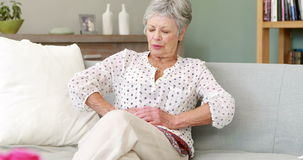 Senior woman suffering with a belly pain. On couch stock footage