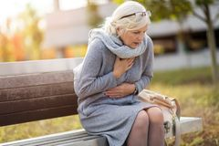 Senior Woman Suffering From Chest Pain. While Sitting On Bench royalty free stock photos