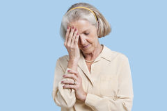 Senior woman suffering from headache against blue background Royalty Free Stock Photography
