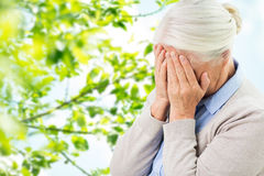 Senior woman suffering from headache or grief. Stress, age and people concept - senior woman suffering from headache or grief over green natural background Stock Photography