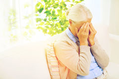 Senior woman suffering from headache or grief. Stress, age and people concept - senior woman suffering from headache or grief over window with green natural Royalty Free Stock Photos
