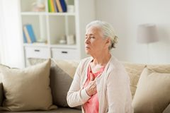 Senior woman suffering from heartache at home. Old age, health problem and people concept - senior woman suffering from heartache at home Stock Image