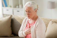 Senior woman suffering from heartache at home. Old age, health problem and people concept - senior woman suffering from heartache at home Stock Images