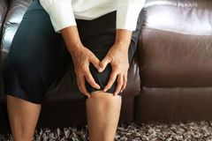 Senior woman suffering from knee pain at home, health problem concept stock photos