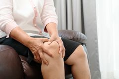 Senior woman suffering from knee pain at home, health problem concept stock photo