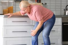 Senior woman suffering from knee pain. In kitchen stock photo