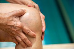 Senior woman suffering from knee pain, Massaging by her hand, Blue swimming pool royalty free stock images