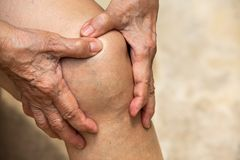 Senior woman suffering from knee pain sitting on chair, Massaging by her hand, Body concept royalty free stock images