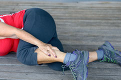 Senior woman suffering from leg cramps royalty free stock image