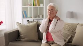 Senior woman suffering from neck pain at home stock video