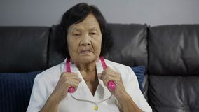 Senior woman suffering from neck pain and massaging by massage assistant tools stock video footage