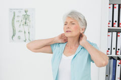 Senior woman suffering from neck pain in medical office Stock Photos