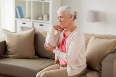 Senior woman suffering from pain in hand at home stock images