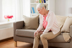 Senior woman suffering from pain in leg at home Stock Photos
