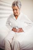 Senior woman suffering from stomach ache. Sitting on bed in bedroom Royalty Free Stock Photo