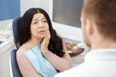 Senior woman suffering from toothache. This pain is unbearable! Senior female patient visiting professional dentist experiencing toothache looking desperate and stock image