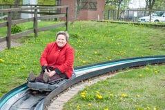 Senior woman on summer sledge run in spring. Senior woman having fun on summer sledge run in spring Royalty Free Stock Photo