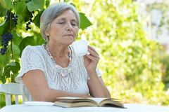 Senior woman in summer at table royalty free stock photography