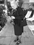 Senior woman on sun terrace. Black and white portrait of senior woman on sun terrace in formal clothes adjusting camera, sun loungers in background royalty free stock photos