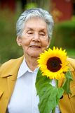 Senior woman with a sunflower Royalty Free Stock Images