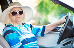 Senior woman in sunglasses driving automobile Stock Photo