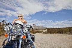 Senior woman in sunglasses poses on motorcycle on desert road Stock Photos