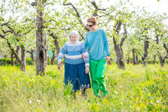 Senior woman supported by granddaughter walking in orchard Stock Photo