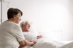 Senior woman supporting sick husband royalty free stock photos