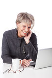 Senior woman surfing the internet. And smiling in amusement at the information on the screen of her laptop computer Royalty Free Stock Photography