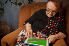 Senior woman surfing the internet on a tablet Royalty Free Stock Images