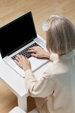 Senior woman surfing the net on laptop at home Stock Photography