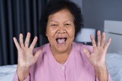 Senior woman with surprised expression. In bedroom stock image