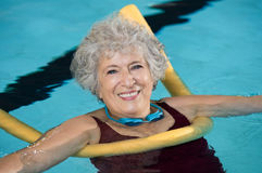 Senior woman swim. Senior woman doing aqua fitness with swim noodles. Mature woman doing water aerobics with a yellow noodle. Old woman in swimming pool doing stock photos