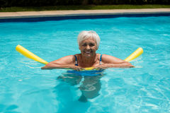 Senior woman swimming with inflatable tube Stock Image