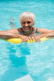 Senior woman swimming with inflatable tube Stock Photo