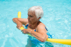 Senior woman swimming with inflatable tube Stock Photos