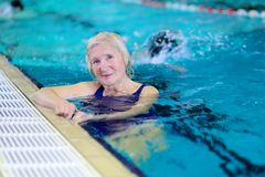 Senior woman swimming in pool Stock Photography