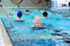 Senior woman swimming in the pool Stock Photos