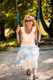 Senior woman on swing portrait Royalty Free Stock Image