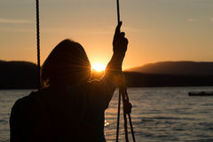 Senior woman on swing with sunset Stock Photo