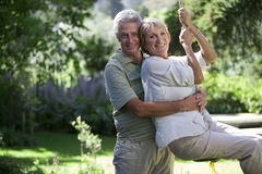 Senior woman swinging on garden rope swing, man embracing woman, smiling, side view, portrait Royalty Free Stock Photos