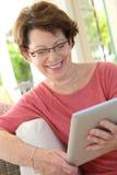 Senior woman on a tablet stock photos