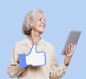 Senior woman with tablet PC holding fake like button against blue background royalty free stock image