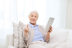 Senior woman with tablet pc showing thumbs up Stock Photos