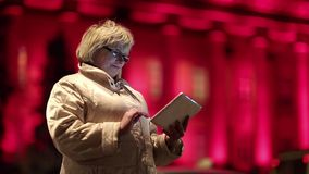 Senior woman with tablet PC stands near the road and red building in nighttime. Businesswoman with glasses stands near the road and uses tablet PC, night city stock footage