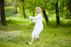 Senior woman Tai chi. Senior woman in white practising tai chi royalty free stock image